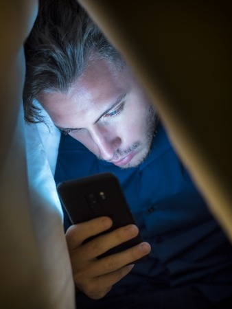 Young man hiding himself under a blanket while using a mobile phone for browsing the internet or for chatting online privately