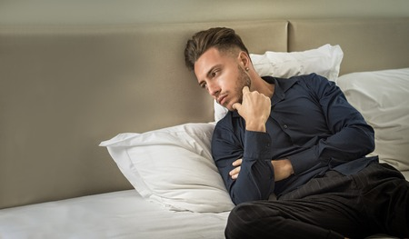 Sexy male model laying alone on bed in his bedroom, looking away to a side with a seductive attitude,, wearing blue elegant shirt 스톡 콘텐츠