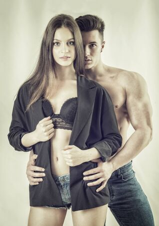 Romantic couple embracing from behind in studio shot, man is muscular and shirtless, woman is showing bra under open shirt, both looking at camera