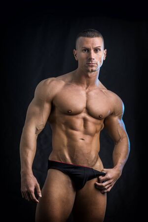 Handsome confident shirtless bodybuilder standing in underwear, looking at camera, on black background