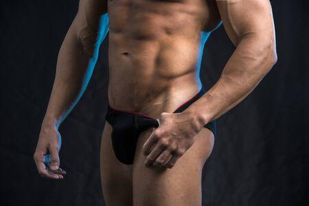Shirtless bodybuilder standing in underwear, on black background