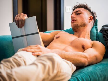 Handsome shirtless athletic young man reading book while laying on couch