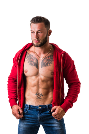 Handsome muscular man with sweater open on naked torso, looking to a side, standing, isolated on white