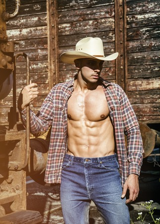 Portrait of young shirtless cowboy with body, jeans and hat posing against of old train while looking at camera