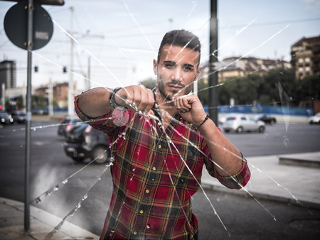 Young macho man in plaid shirt holding fist forward breaking glass and looking at camera