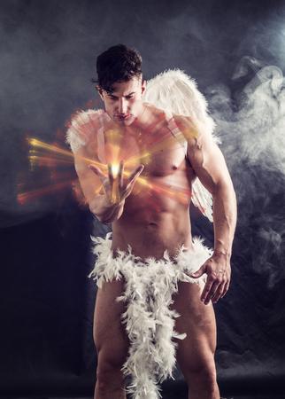 Ángel masculino desnudo sentado en la oscuridad con alas de plumas blancas que se extienden desde su espalda, sosteniendo una bola de energía en la mano