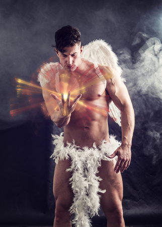 Naked male angel sitting in dark with white feather wings spreading from his back, holding ball of energy in hand