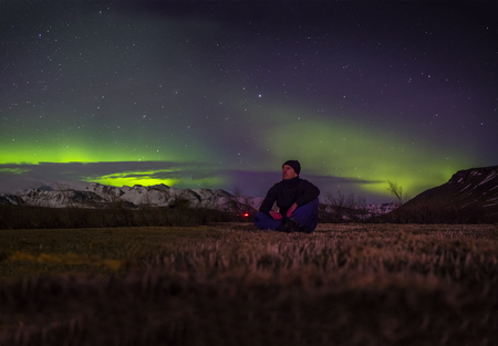 Male traveler sitting on ground and enjoying amazing polar lights at night sky during trip through Iceland