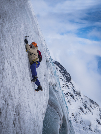 Side view of male in warm clothes climbing icy slope of mountain against cloudy sky in Iceland