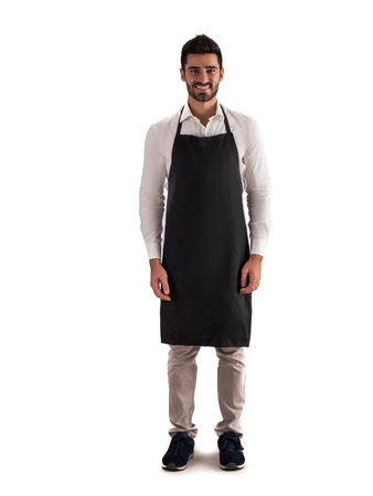 Full length shot of young chef or waiter posing, wearing black apron and white shirt isolated on white background Фото со стока