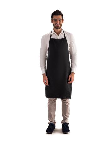 Photo de toute la longueur d'un jeune chef ou d'un serveur posant, portant un tablier noir et une chemise blanche isolée sur fond blanc Banque d'images