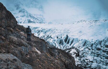 Rückansicht eines professionellen Bergsteigers in warmer Kleidung, der auf einem eisigen Oberflächengletscher von einem schneebedeckten Berg in Island spaziert? Standard-Bild