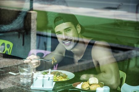 Attractive Young Man Eating Salad in Diner, vu de l'extérieur à travers la fenêtre. Regarder la caméra Banque d'images