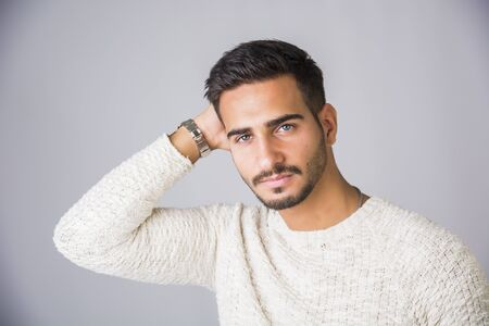 Handsome young man wearing white sweater, on light background in studio shot