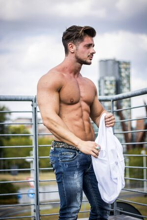 Handsome Muscular Shirtless Hunk Man Outdoor in City Setting. Showing Healthy Body While Looking Away Stock Photo