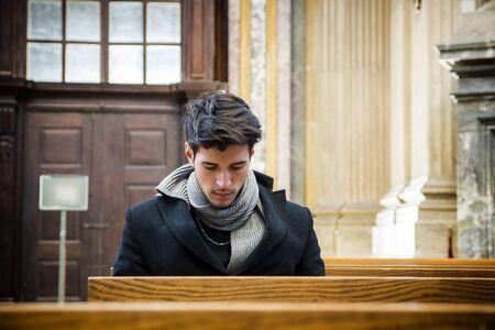 Młody mężczyzna siedzi i klęczy w kościele, modląc się, na drewnianej ławce