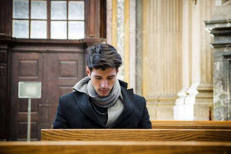Young man sitting and kneeling in church praying, on wood bench