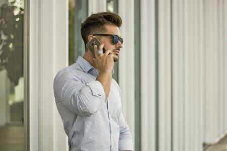 Handsome man calling on cellphone, wearing elegant shirt posing outside on urban background. Фото со стока