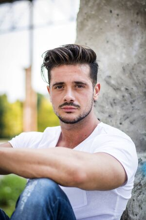 Handsome fit man in white t-shirt outdoor in city setting, looking at camera Фото со стока