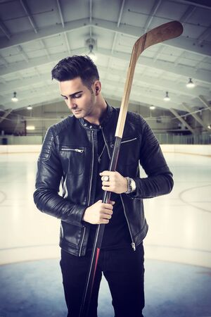 Portrait of a handsome man in blue hoodie posing for camera with hockey stick in his hands Фото со стока