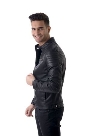 Young handsome man standing in studio shot, isolated on white, wearing black leather jacket and black jeans