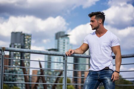 Handsome fit man in white t-shirt outdoor in city setting, looking away
