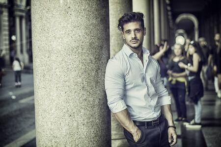 Stylish handsome man wearing elegant shirt, outside in urban setting, looking at camera