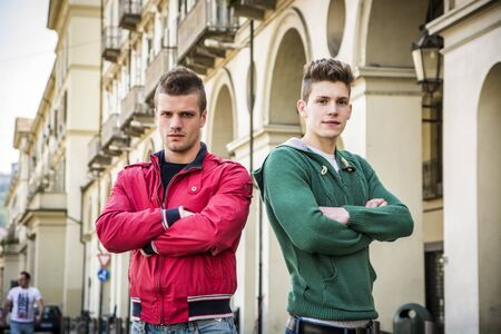 Two young male friends standing in European city center, looking at camera with arms crossed on chest