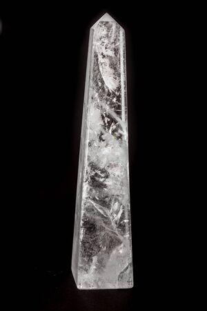 Beautiful cut white quartz obelisk stone on dark surface.