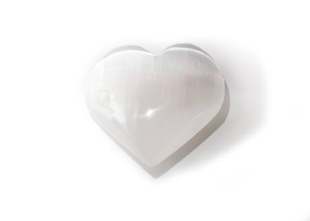 Beautiful white selenite heart shaped mineral, cut and polished, on white background, isolated