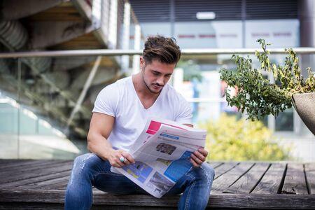 Hombre guapo leyendo el periódico al aire libre en el entorno de la ciudad, sentado en los pasos