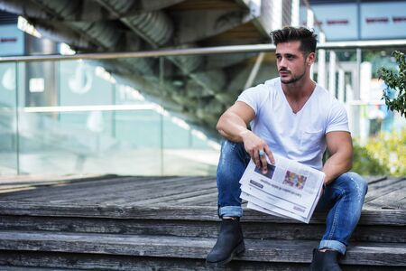 Handsome man reading newspaper outdoor in city setting, sitting on steps Фото со стока