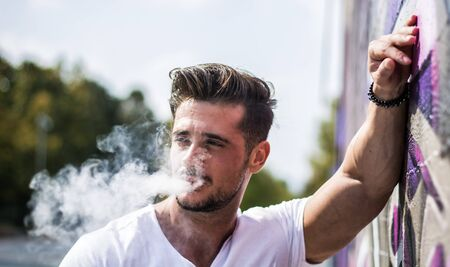 Handsome man smoking e-cigarette, vaping outdoor in city setting