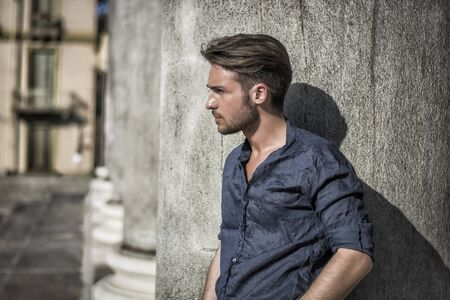 One handsome young man in urban setting in summer day, wearing blue shirt, leaning against stone column or pillar