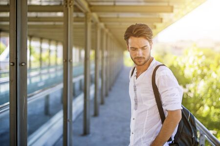 Handsome fit man in white shirt outdoor in city setting, looking away