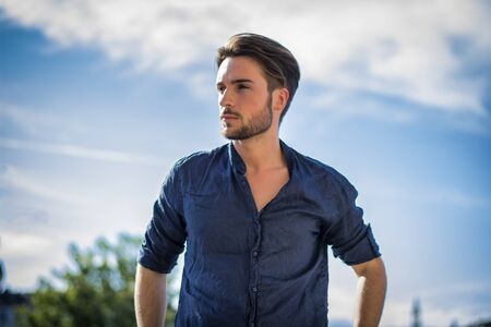 One handsome young man in urban setting in summer day, wearing blue shirt Фото со стока
