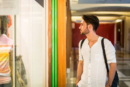 Handsome Young Man in White Shirt and Backpack Looking at Displayed Fashion Items in Glass Window Boutique at the Street Side.