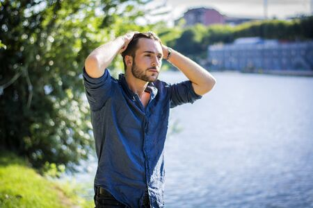 One handsome young man in urban setting in European city, Turin in Italy by the river Po