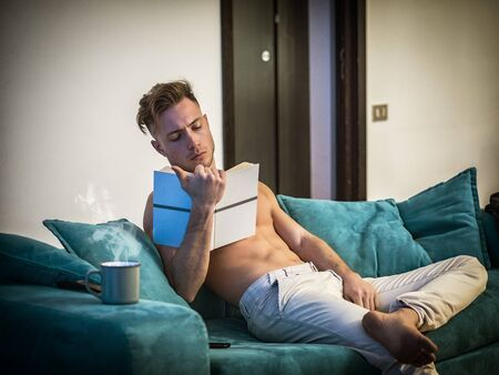 Handsome shirtless athletic young man reading book while sitting on couch Standard-Bild
