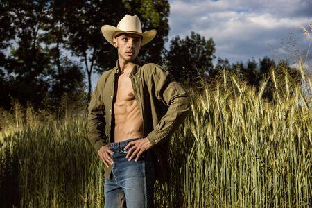 Retrato de granjero o vaquero con sombrero con camisa desabrochada en torso musculoso, mirando hacia un lado, mientras está de pie junto al campo de heno en el campo Foto de archivo