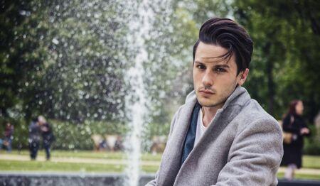 Elegant attractive young man outdoor wearing wool coat, in European city