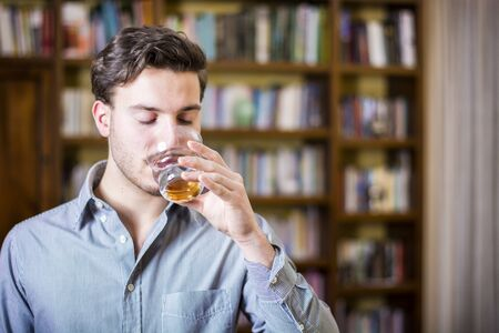 Young man in shirt drinking water from crystal glass on background of bookshelves.