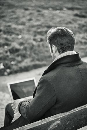 Handsome elegant businessman sitting on a wooden bench working outdoors in an urban park typing information onto his laptop computer, seen from the back