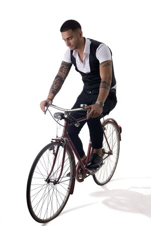 Portrait of young tattooed man in elegant clothes riding a bicycle. Studio shot. Full body shot