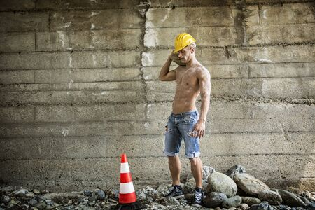 Sexy, muscular construction worker shirtless, working outdoor, wearing blue jeans and yellow hard-hat