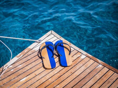From above of pair of colorful flip flops placed on floating wooden platform near clean blue water on resort