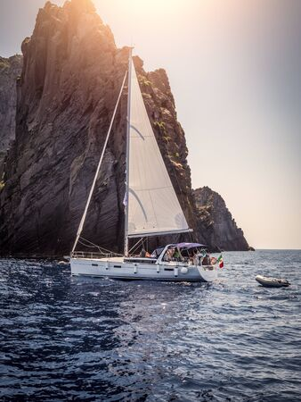 Modern white yacht sailing slowly in rippling sea near rough rock in cloudless evening on resort