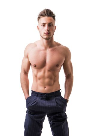 Handsome shirtless athletic young man wearing only pants, with blue eyes, looking at camera in studio shot, isolated on white background