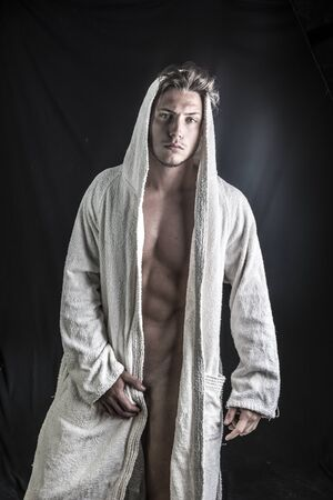 Handsome totally naked young man wearing white bathrobe, on dark background in studio shot
