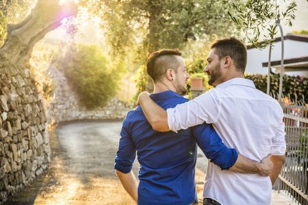 Stylish handsome men walking on nice road. Gay couple outdoor